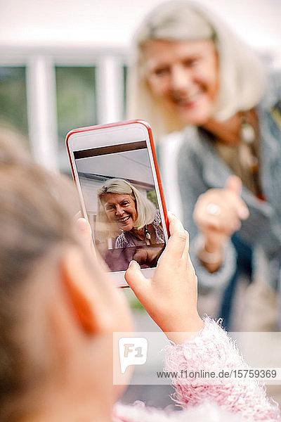 Enkelin fotografiert Großmutter mit einem Mobiltelefon