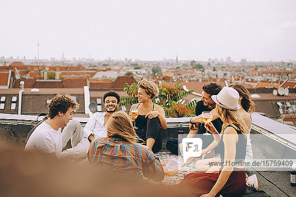 Friends enjoying beer while sitting together on terrace at rooftop party