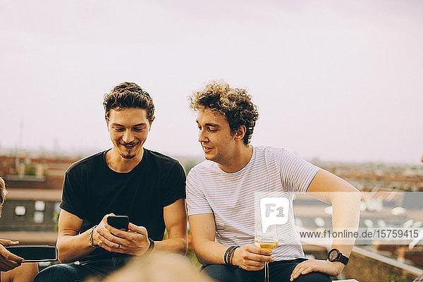 Mann zeigt einem Freund sein Handy und trinkt während der Party auf der Terrasse
