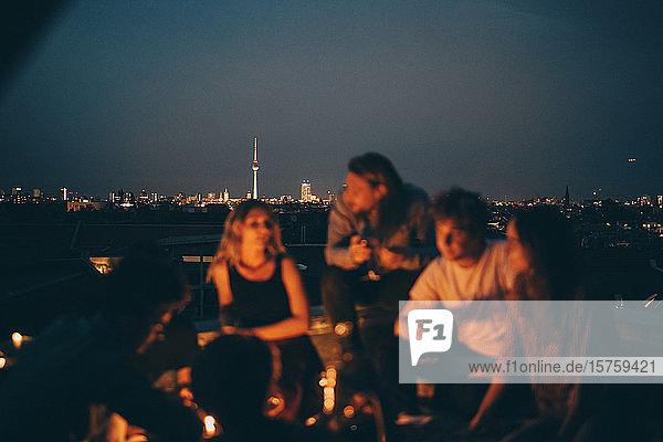 Freunde genießen in der Dämmerung auf der Terrasse gegen das Stadtbild