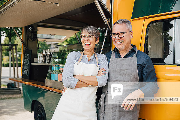Happy mature couple looking away while standing against food truck