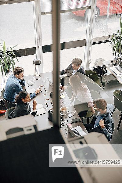 Hochwinkelansicht von Kollegen  die am Schreibtisch im Coworking Space arbeiten