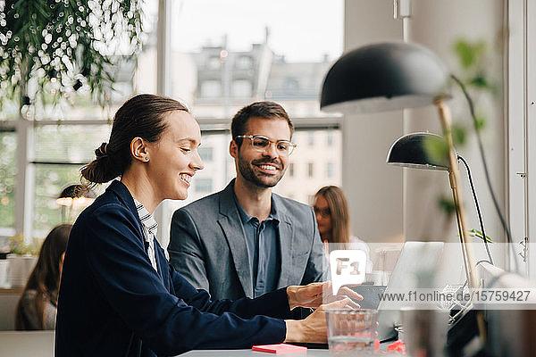 Männliche und weibliche Geschäftskollegen diskutieren am Laptop am Schreibtisch im Kreativbüro