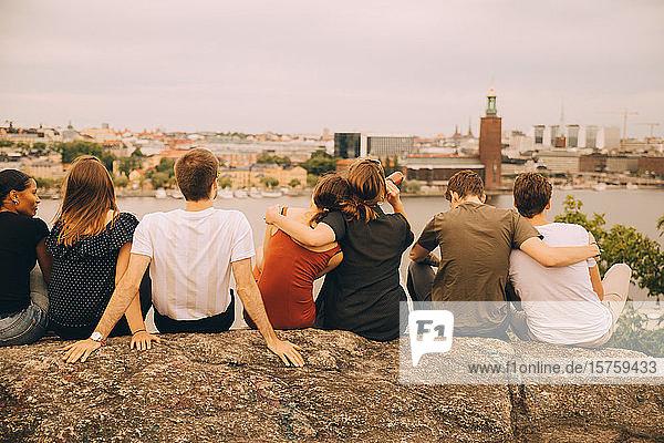 Rückansicht von Freundinnen und Freunden  die auf einer Felsformation in der Stadt sitzen