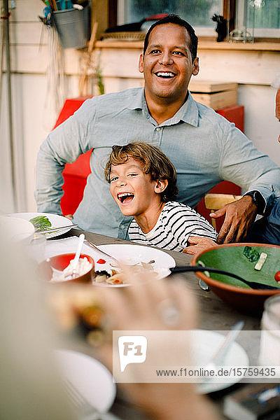 Lächelnder Vater und Sohn sitzen während des Familienmittagessens am Esstisch