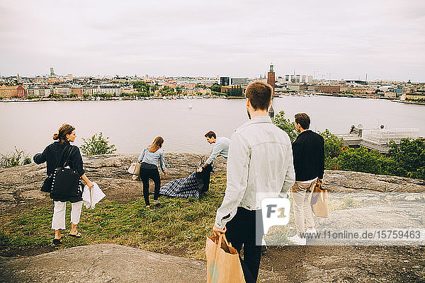 Hochwinkelaufnahme von Freunden  die sich im Sommer für ein Picknick auf einem Feld am See vorbereiten