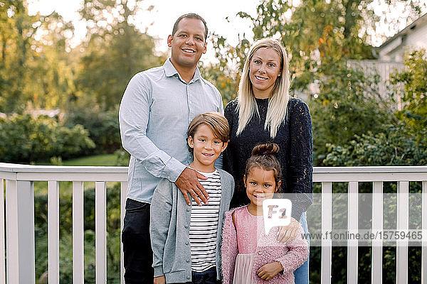 Porträt einer lächelnden Familie  die im Hinterhof an einem Geländer steht