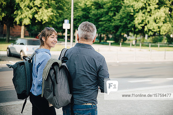 Happy female talking to mature man while walking in city