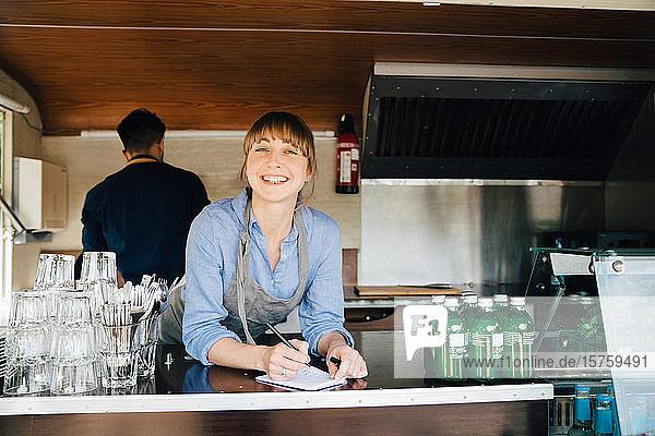 Porträt einer glücklichen Besitzerin  die im Speisewagen steht  während ihre Kollegin im Hintergrund arbeitet