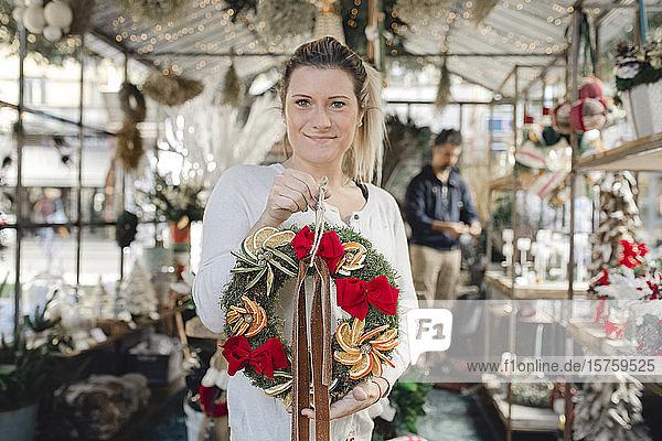 Frau hält Weihnachtskranz im Geschäft