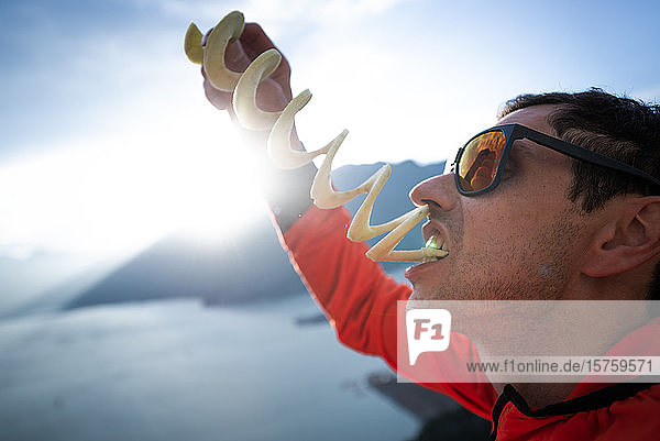 Bergsteiger isst Kartoffel-Twister gegen pralle Sonne  Squamish  Britisch-Kolumbien  Kanada