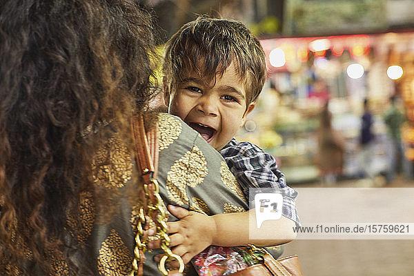 Mutter trägt aufgeregten kleinen Jungen im Basar