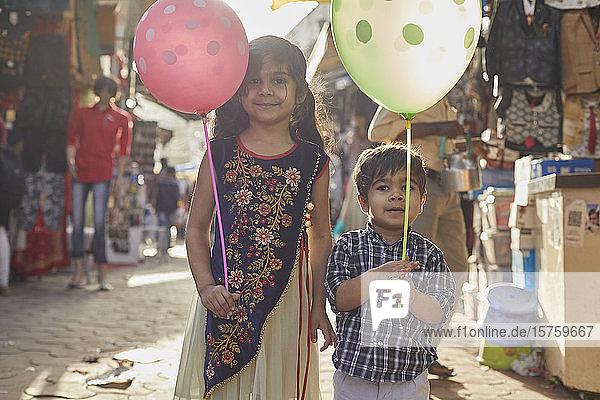 Geschwister mit Luftballons beim Basarspaziergang