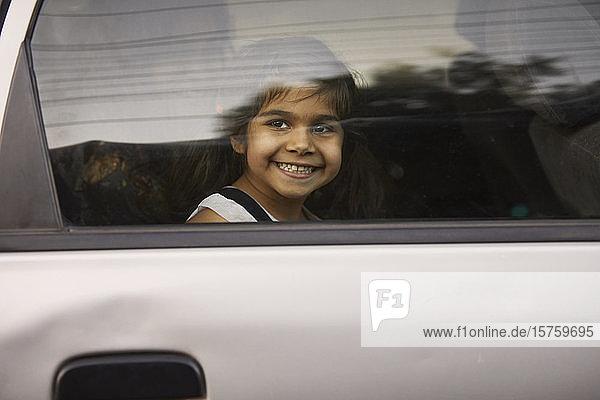 Kleines Mädchen schaut durch ein Autofenster hinaus