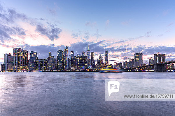 View across the water of New York City  Manhattan island  at dawn  flat calm water.