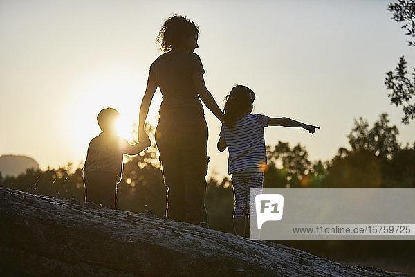 Mutter und Kinder erkunden die Natur bei Sonnenuntergang