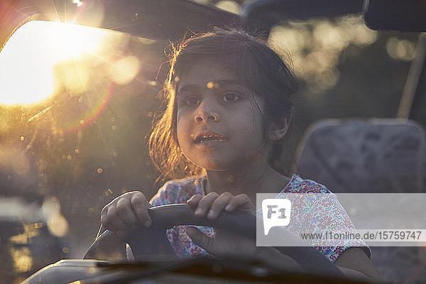 Kleines Mädchen hinter den Rädern eines Fahrzeugs