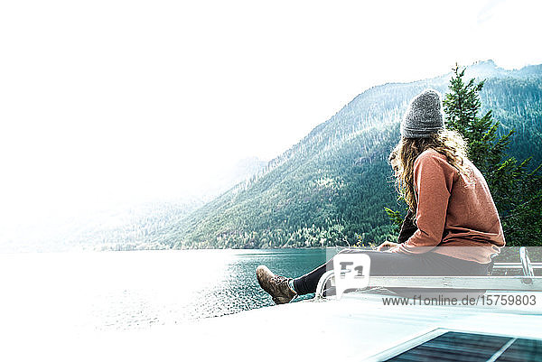 Woman seated on top of campervan overlooking the lake  Cathedral Grove  British Columbia  Canada