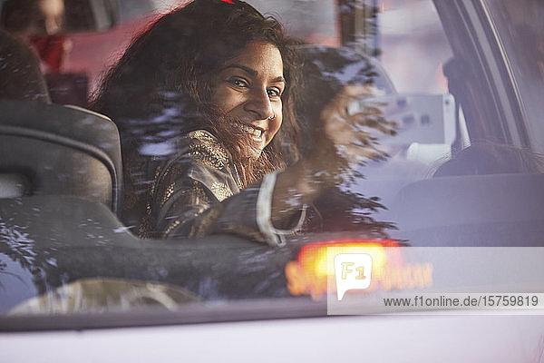 Frau dreht sich um und fotografiert im Fahrzeug