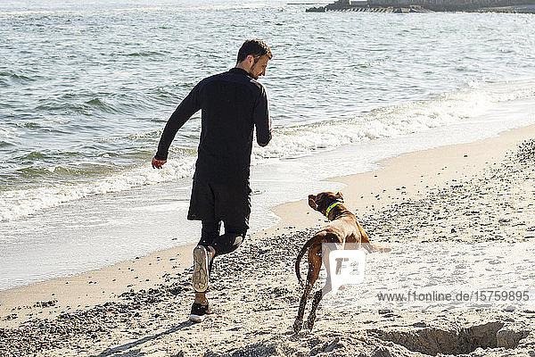 Mann joggt mit Hund am Strand