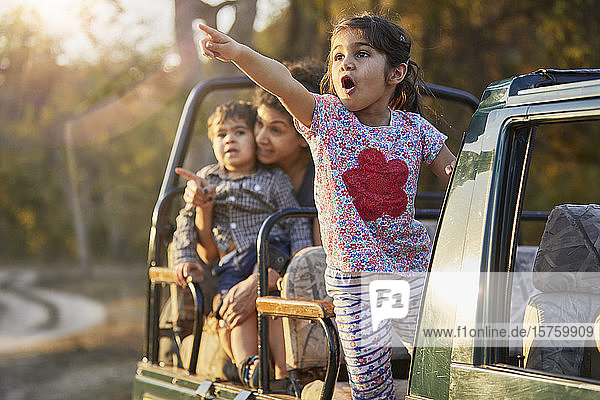 Mother and children enjoying nature from off road vehicle