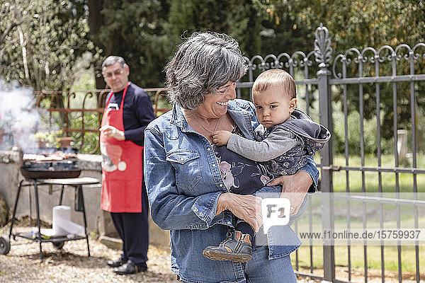 Grossmutter trägt einen kleinen Jungen beim BBQ-Treffen der Familie  Florenz  Italien