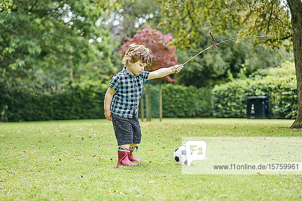 Toddler playing with stick and football in park