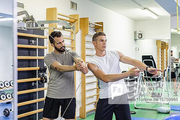 Mann trainiert Freund im Fitnessstudio