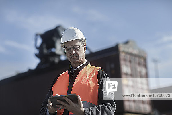 Ingenieur mit digitalem Tablett am Hafen