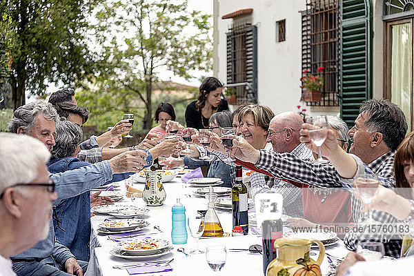Family toasting at outdoor lunch in garden  Florence  Italy