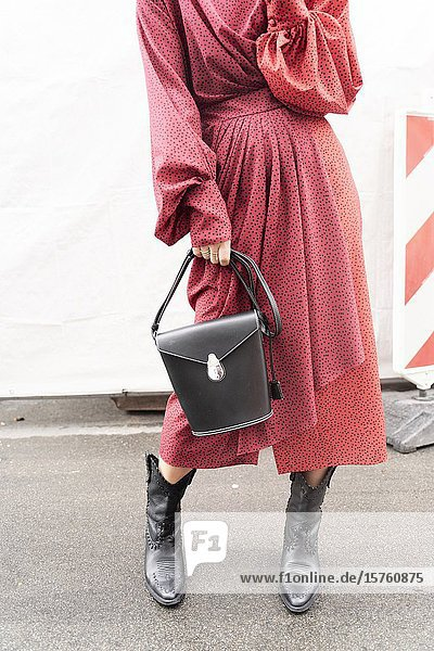 Fashionable woman in a red dress  holding a handbag. Munich  Germany.