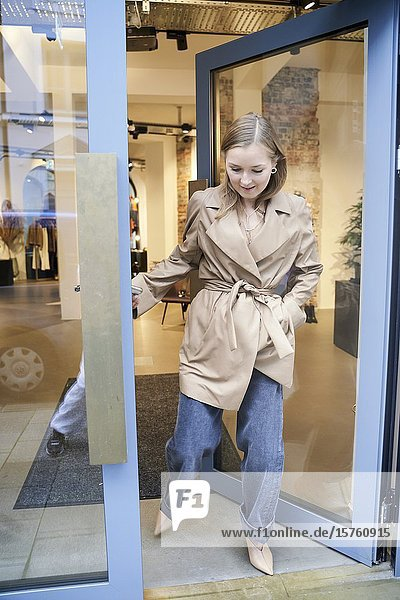 Fashionable woman leaving a clothing store. Munich  Germany.