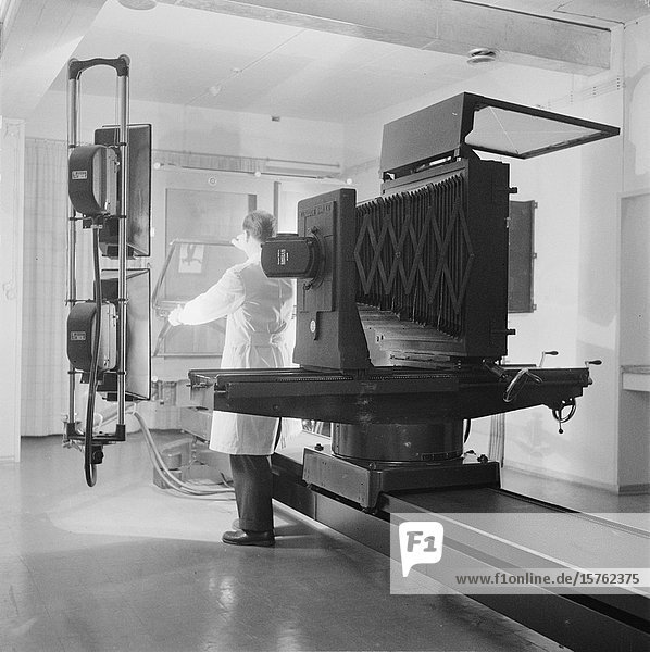 Photographer using large plate camera in printing works studio  Finland 1959