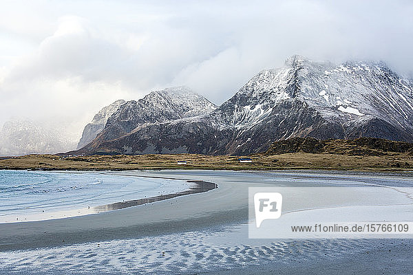 Mountains and remote ocean beach Ytresand Lofoten Norway