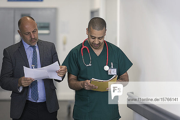 Male administrator and surgeon reading paperwork in hospital corridor