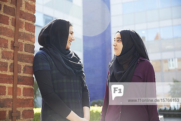 Young women in hijabs talking outside sunny building