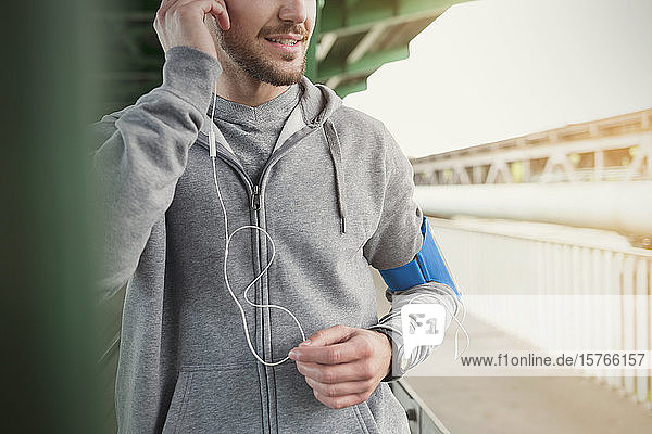 Male runner listening to music with headphones and mp3 player