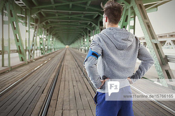 Young male runner standing on train tracks with hands on hips