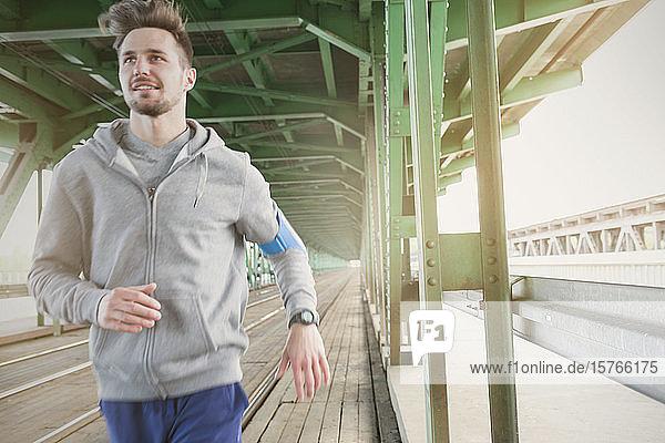 Young male runner running along urban train tracks