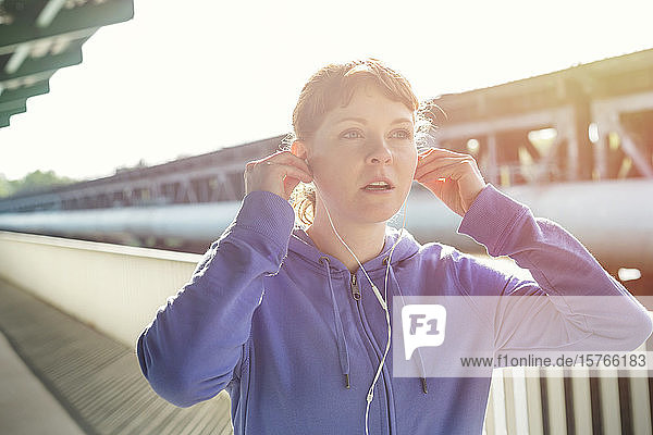 Young female runner adjusting headphones  listening to music