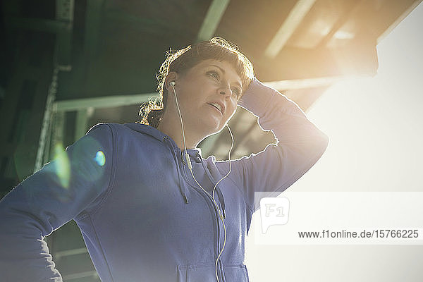 Young female runner with headphones resting