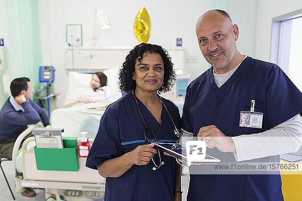 Porträt selbstbewusster Ärzte mit digitalem Tablet bei der Visite im Krankenhauszimmer