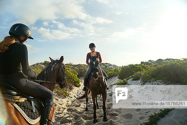 Young women horseback riding on sunny beach