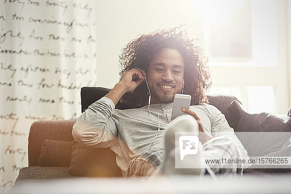 Young man relaxing  listening to music with headphones and mp3 player on sofa