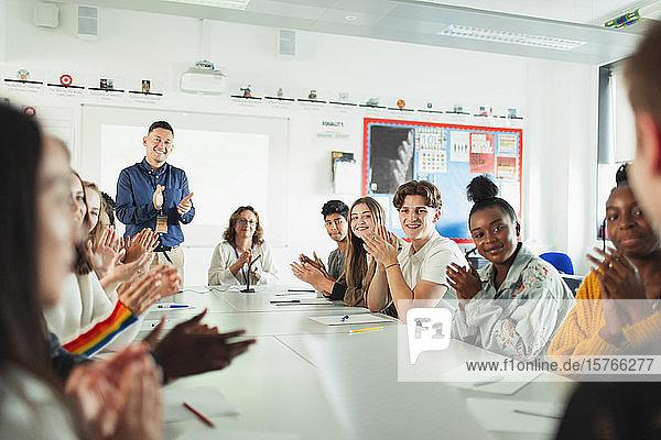 High school students and teacher clapping debate class
