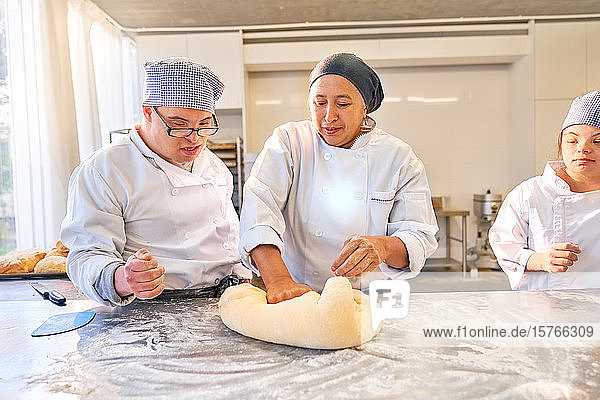 Instructor teaching students with Down Syndrome how to roll dough