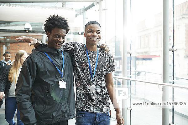 Happy high school boy friends walking in corridor