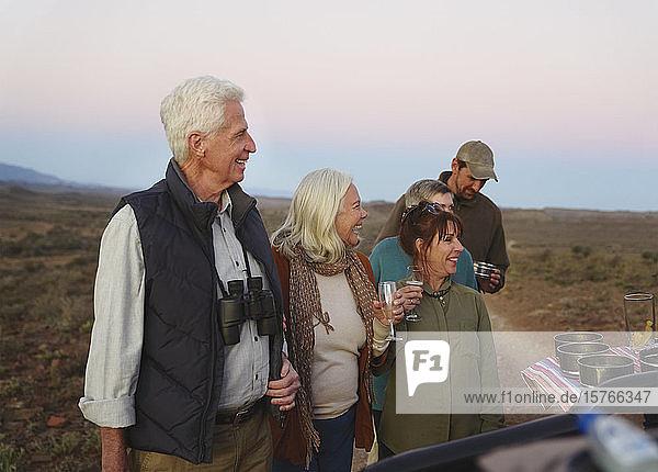 Glückliches Seniorenpaar auf Safari trinkt Champagner
