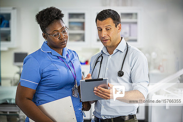 Male doctor with digital tablet talking with female nurse in hospital