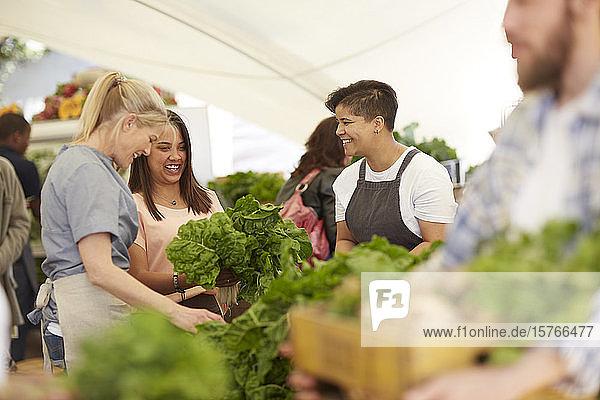 Women working  arranging vegetables at farmer's market Women working, arranging vegetables at farmer's market